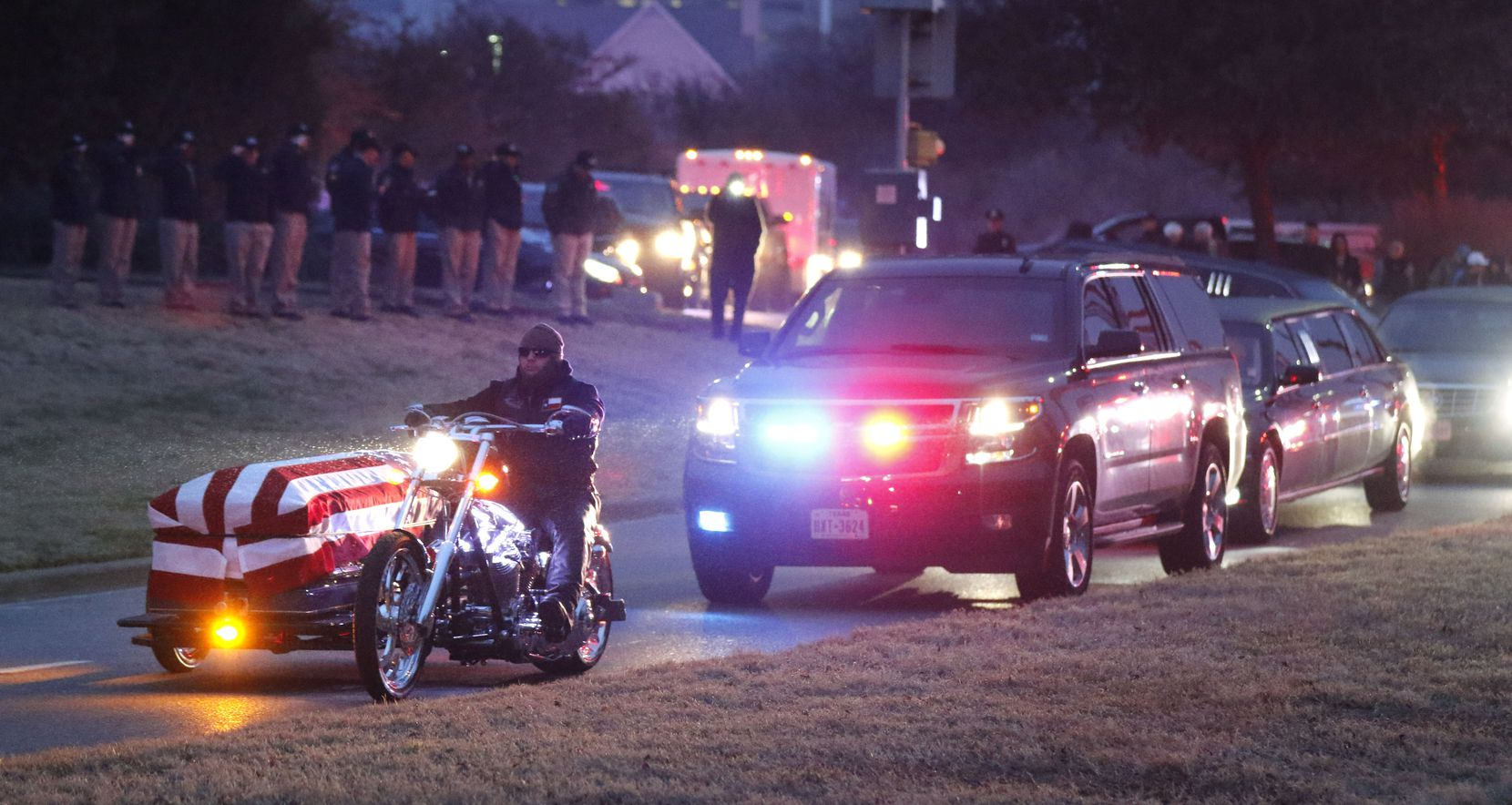 Law enforcement officers salute as a motorcycle carrying Richardson police officer David Sherrard after his funeral at Watermark Community Church in Dallas, Texas, Tuesday, February 13, 2018.