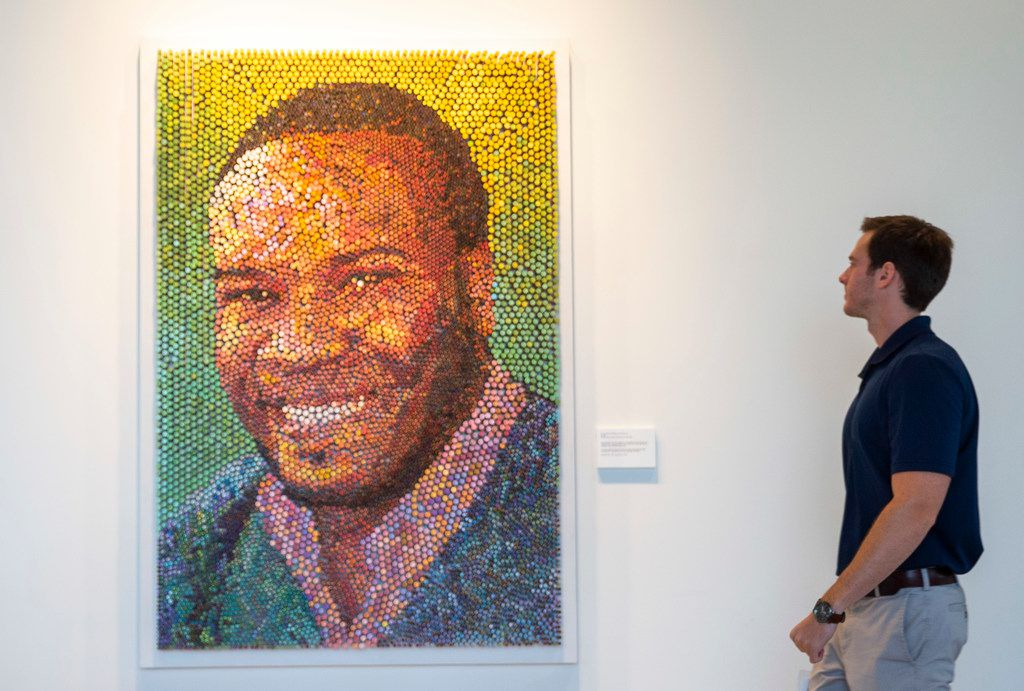 Andrew Veazey looks at artwork of Botham Jean as it hangs hangs on the wall  on Wednesday, October 2, 2019 at the PricewaterhouseCoopers office in Dallas.