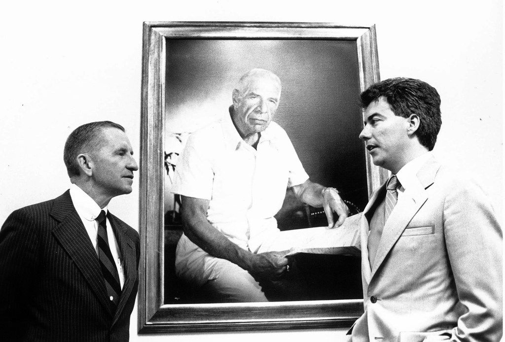 "Ross Perot, left, and Ken Follett, author of On Wings of Eagles, at EDS headquarters in 1983, stand with a portrait of Arthur ""Bull"" Simons, who led the raid that freed two EDS hostages from a prison in Iran."
