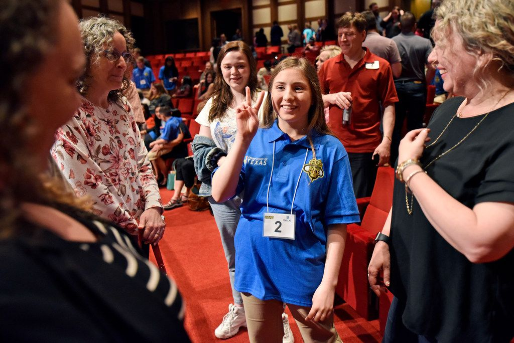 Spelling bee competitor Ruth Davie, center, of Dallas, showed a peace sign as she met with family and friends during a break at the 61st annual Golden Chick Dallas Regional Spelling Bee at the George W. Bush Presidential Center on the campus of Southern Methodist University in Dallas, Saturday, March 9, 2019. Despite not making the final four spellers, Davie's friends and family were excited to see her compete.