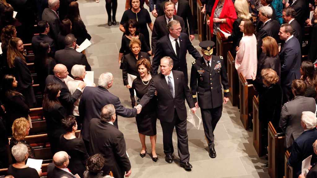 Former President George W. Bush and first lady Laura Bush are greeted by well-wishers during the funeral recessional for George H.W. Bush, the 41st president, at St. Martin's Episcopal Church in Houston.