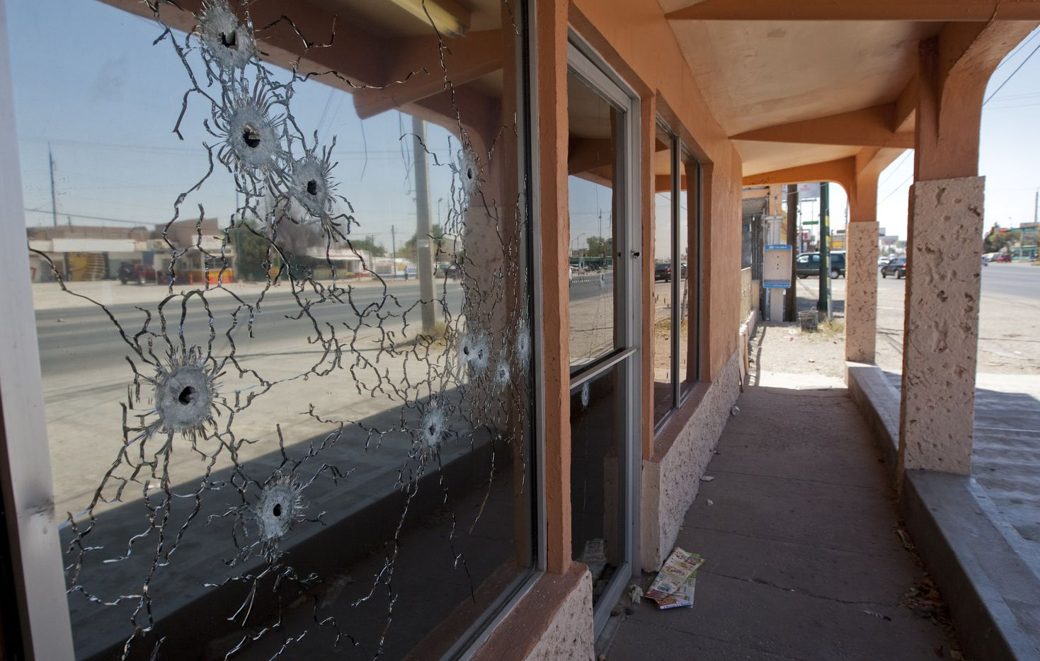 Bullet holes on a window of funeral parlor, one of many businesses that were burned down for not paying a monthly tax charged by criminal gangs to thousands of local businesses in Ciudad Juarez, Mexico, on July 6, 2011.
