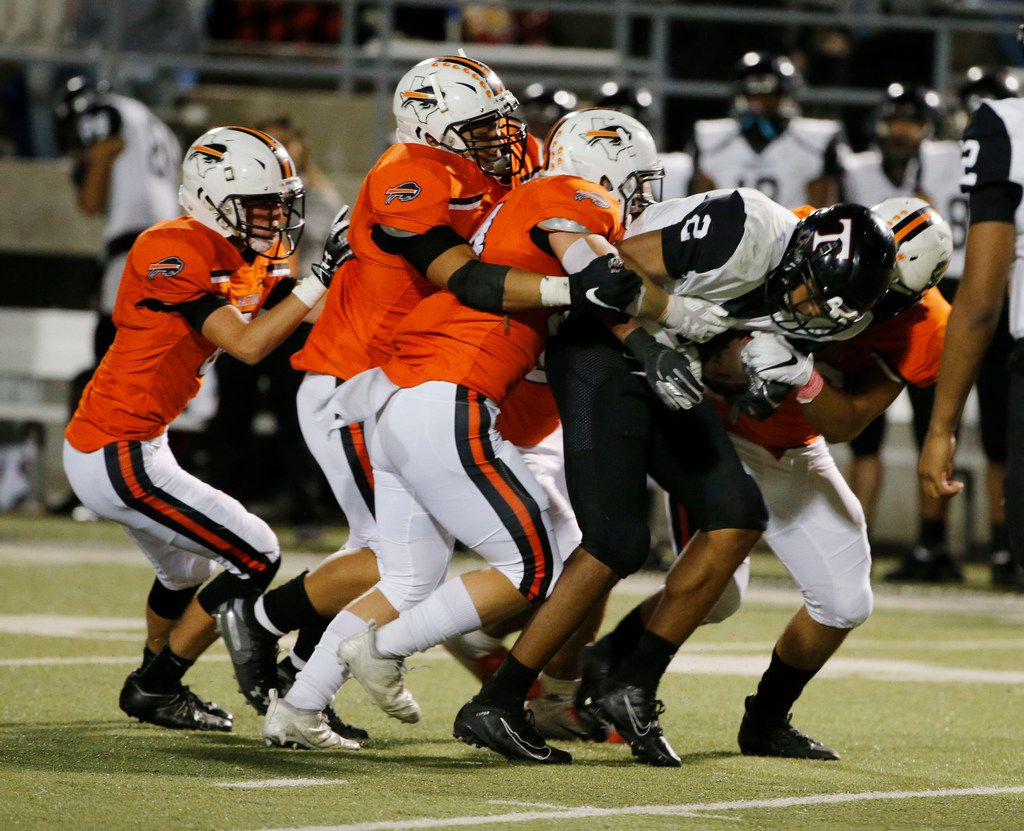 Euless Trinity running back Ollie Gordon (2) is gang tackled by Haltom defenders during the second half of their high school football game on Oct. 11, 2019 in North Richland Hills. Haltom defeated Trinity 23-20. (Michael Ainsworth/Special Contributor)