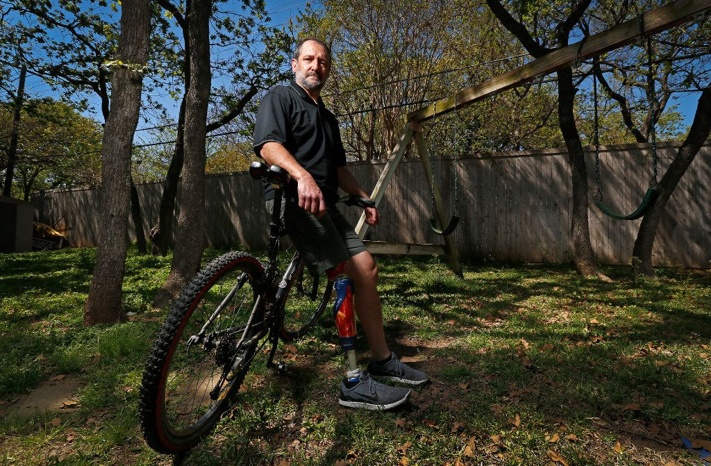 Michael Orlie sits on a mountain bike in the backyard of his home on Tuesday, March 21, 2017, in Arlington, Texas. He lost his leg to cancer when he was 27, and now has a prosthetic limb and pays more than $1,800 per month for the health insurance. (Jae S. Lee/The Dallas Morning News)