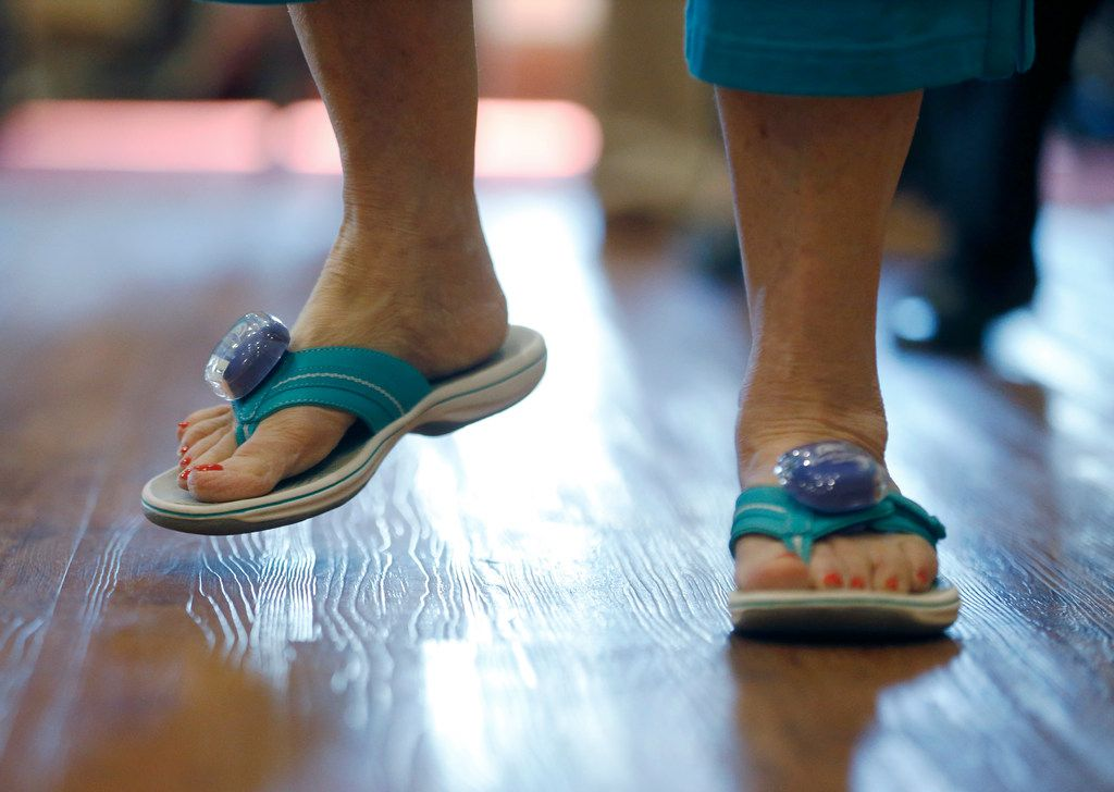 Betty Means wears step counters on her sandals during a line dancing class.