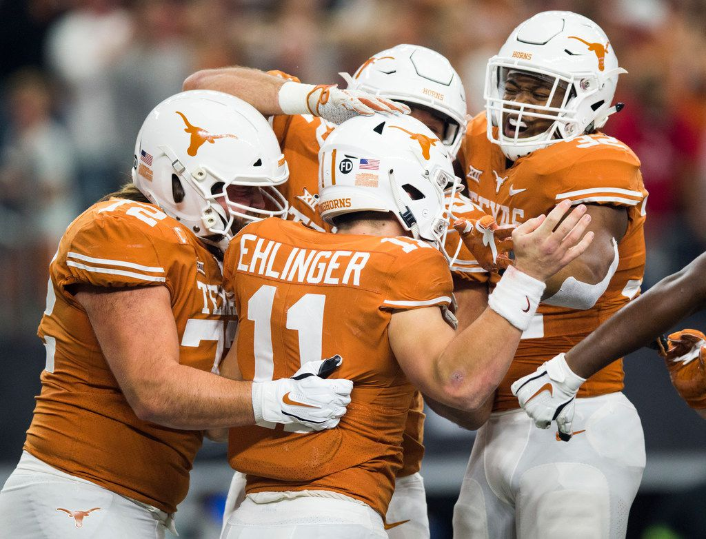 FILE - Texas Longhorns quarterback Sam Ehlinger (11) celebrates with team mates in the endzone after scoring a touchdown during the first quarter of the Big 12 Championship football game between the Texas Longhorns and the Oklahoma Sooners on Saturday, December 1, 2018 at AT&T Stadium in Arlington, Texas. (Ashley Landis/The Dallas Morning News)