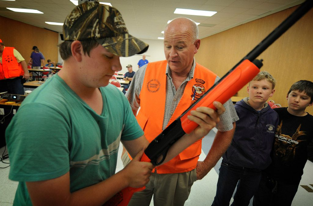 Brandon Yates, left, 16, of McPherson, Kan., holds a demonstration semi automatic shot gun as he talks with Tom Witham, a hunter safety trainer, during training Nov. 1, 2016, in Salina, Kan. (Tom Dorsey/Salina Journal via AP)
