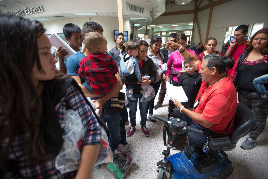 Immigrants wait to be picked up by volunteers from Catholic Charities of the Rio Grande Valley after being dropped off by federal immigration staff at the bus station in McAllen, Texas, on June 10, 2018.  These immigrants now face deportation hearings in the civil immigration courts later.