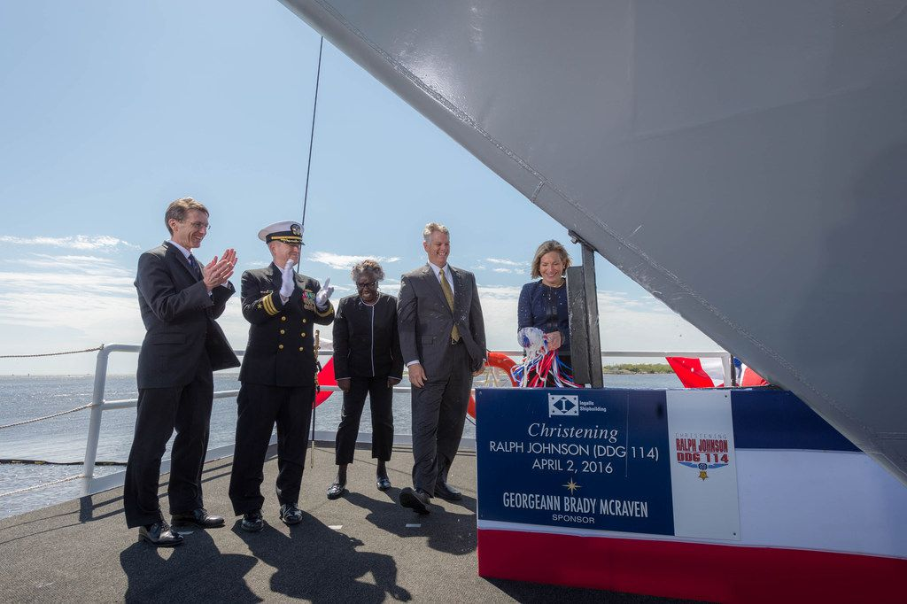 Georgeann McRaven christens the USS Ralph Johnson, a guided missile  destroyer, on her first blow to the bow on April 2, 2016.