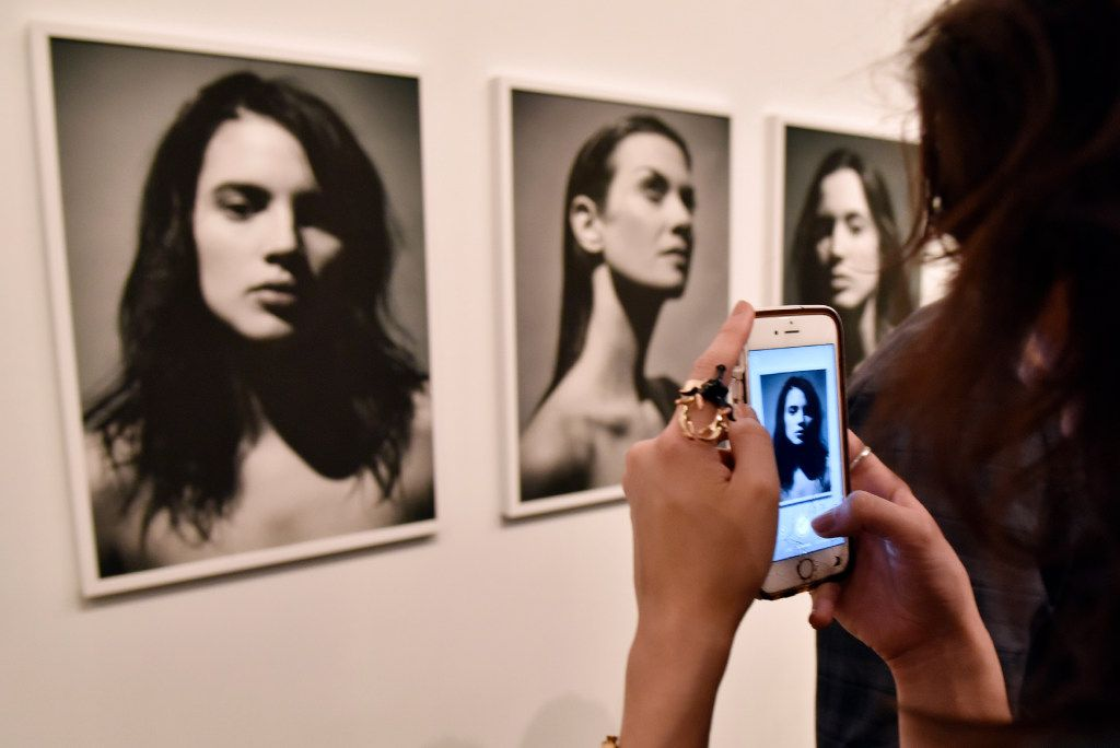 Model Julian Machann takes a picture of her photograph during opening night of Fredrik Broden's exhibit.