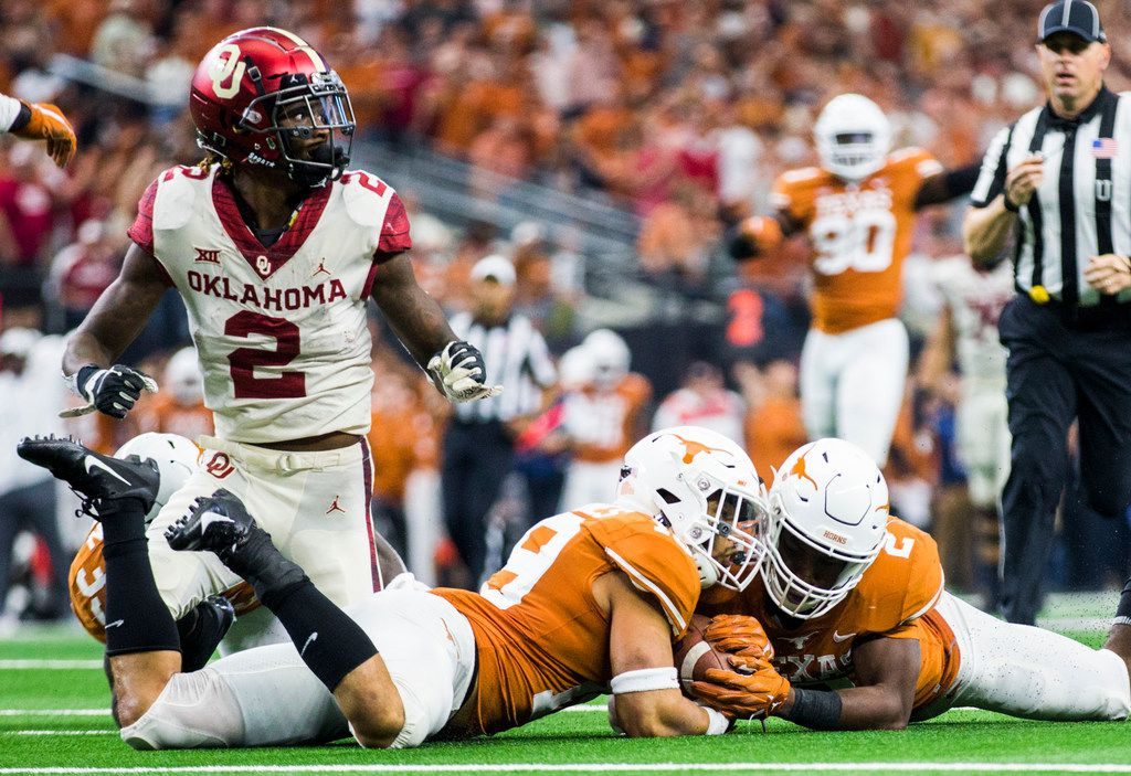 Texas Longhorns defensive back Brandon Jones (19) and defensive back Kris Boyd (2) recover a fumbled ball by Oklahoma Sooners wide receiver CeeDee Lamb (2) during the fourth quarter of the Big 12 Championship football game between the Texas Longhorns and the Oklahoma Sooners on Saturday, December 1, 2018 at AT&T Stadium in Arlington, Texas. (Ashley Landis/The Dallas Morning News)