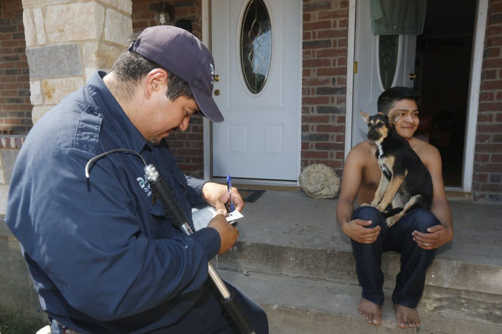 Dallas Animal Services animal control officer Esteban Rodriguez writes a ticket to Martin Rueda, 21, who left his dog loose on the porch or his home in Dallas, on Thursday, Aug 13, 2015.   (Michael Ainsworth/The Dallas Morning News)