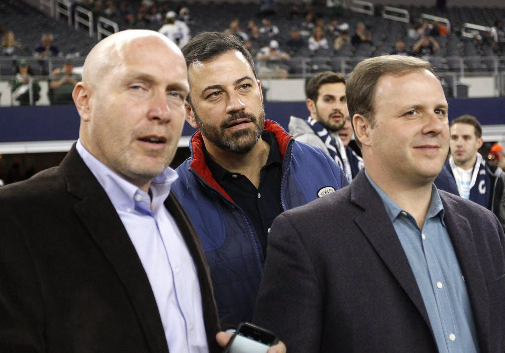 Television host Jimmy Kimmel, center, Sal Iacono, right, and an unidentified person, left, watch the Dallas Cowboys and New York Jets warm up before an NFL football game, Saturday, Dec. 19, 2015, in Arlington, Texas.