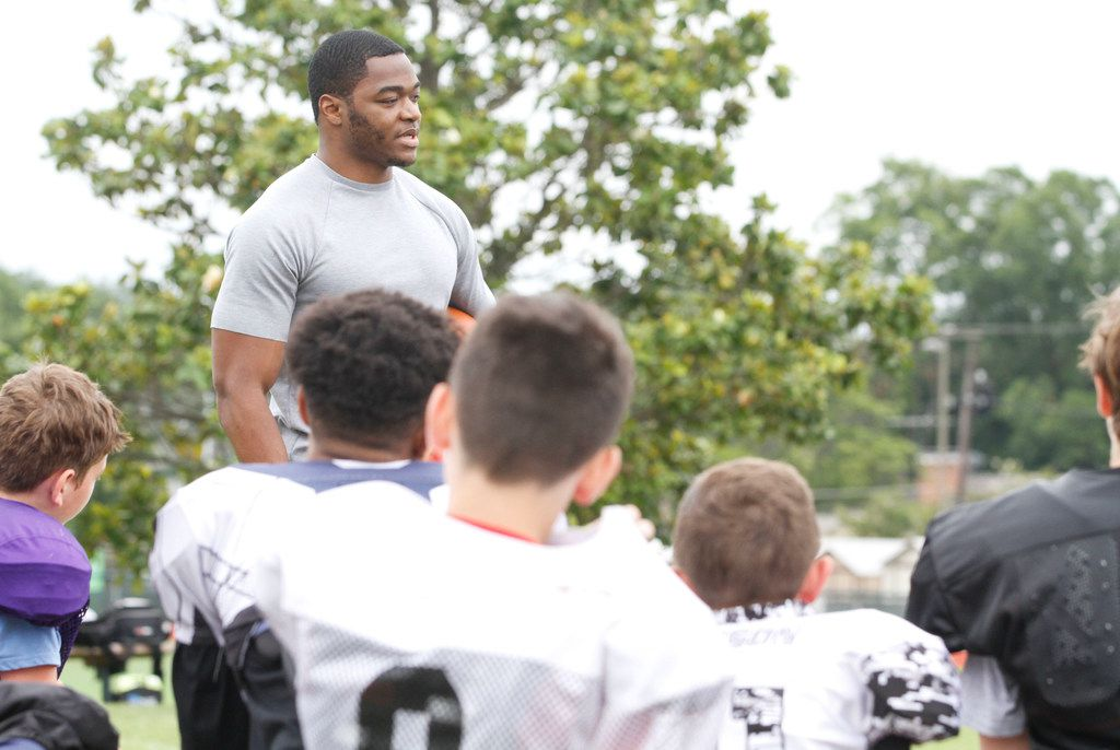 Dallas Cowboys wide receiver Amari Cooper talks to young football players about the importance of hydration at the Offense Defense Football Camp at Hockaday School in Dallas on Monday, June 24, 2019. (Brian Elledge/The Dallas Morning News)