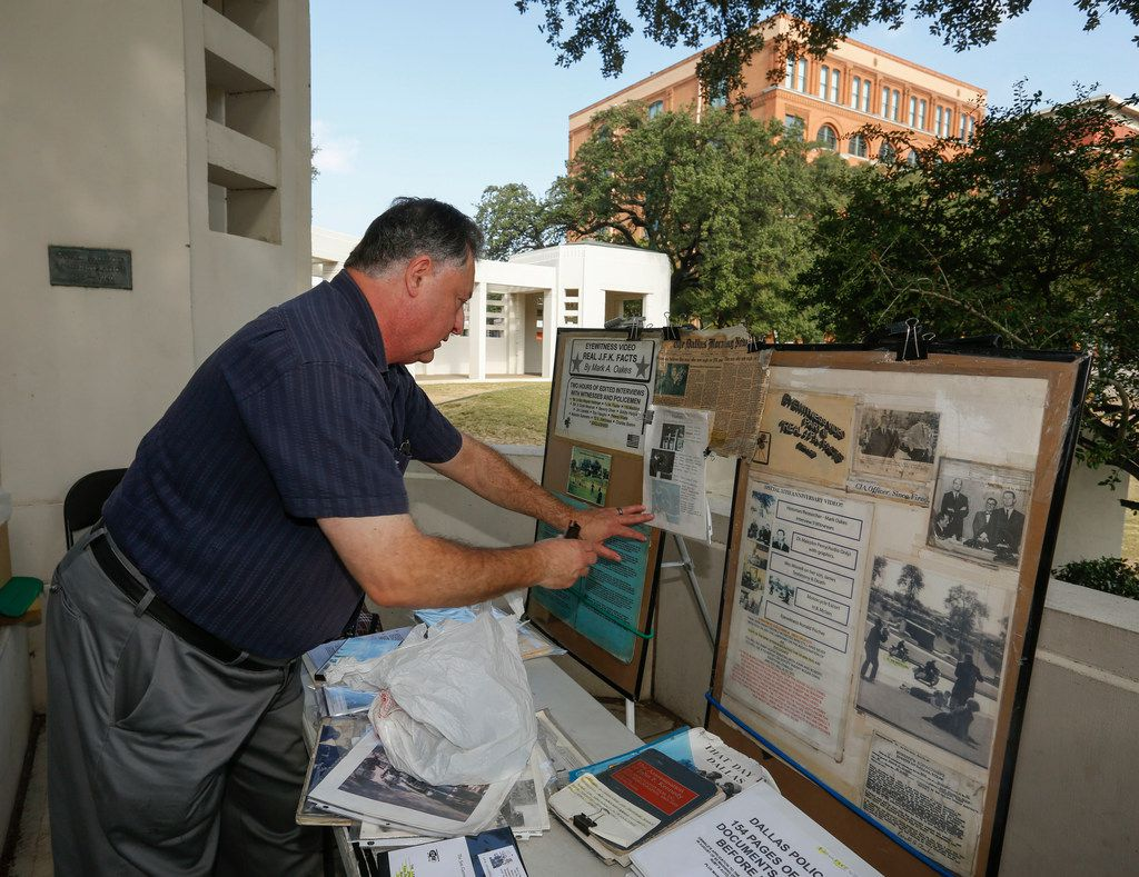Mark A. Oakes, a JFK assassination researcher, sets up his display at Dealey Plaza. Oakes has been at Dealey Plaza selling various videos on the Kennedy assassination since 1995. In the background is the Texas School Book Depository building, now home to the Sixth Floor Museum.