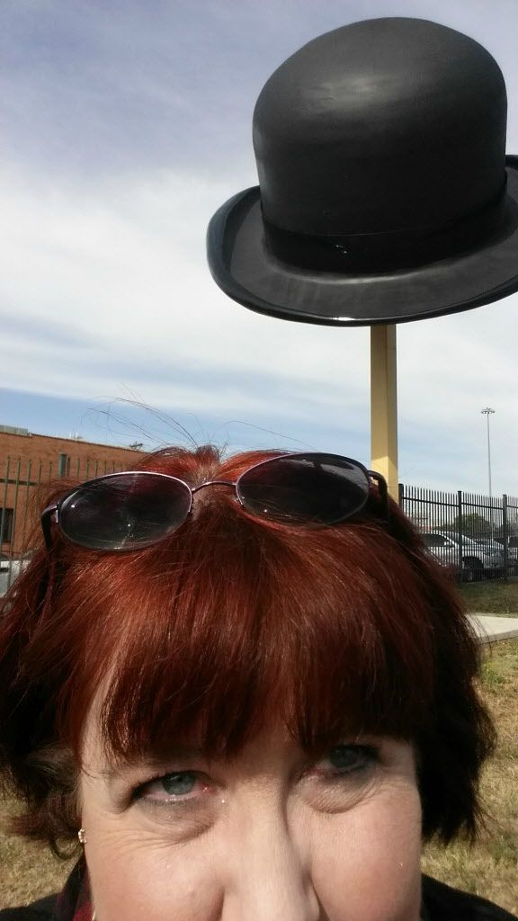 Joy Tipping in front of the giant bowler hat in the Southside area south of downtown Dallas.