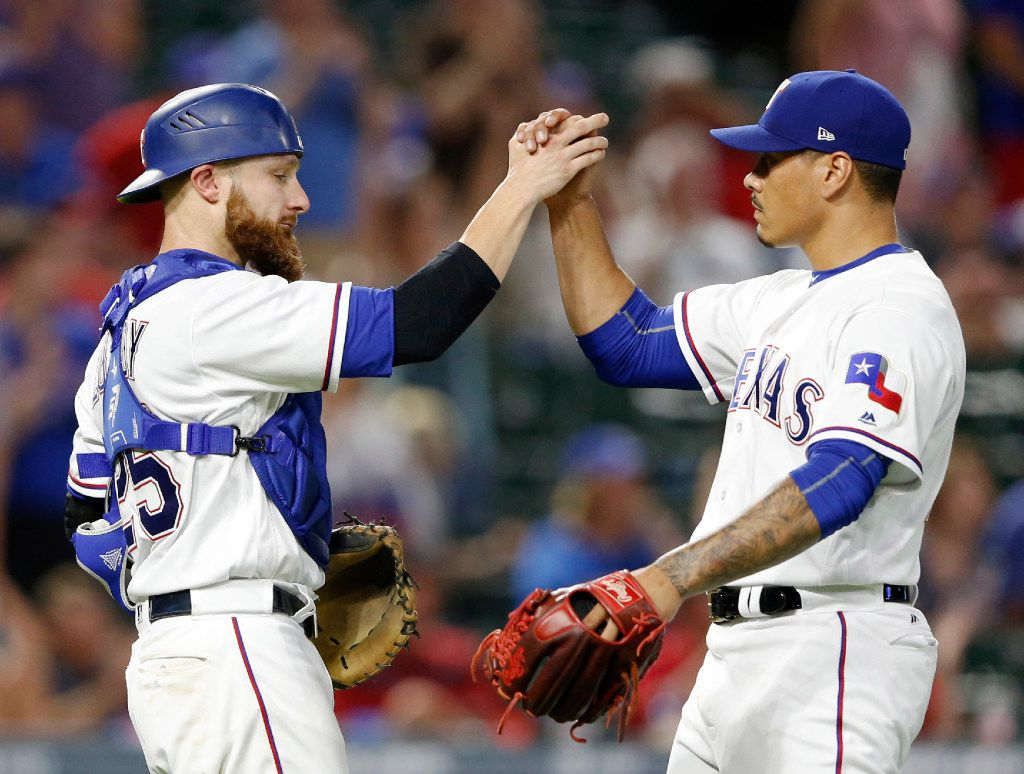 Texas Rangers catcher Jonathan Lucroy (25) and Texas Rangers relief pitcher Keone Kela (50) celebrate a victory over the Toronto Blue Jays, 6-1at Globe Life Park in Arlington on Tuesday, June 20, 2017. (Vernon Bryant/The Dallas Morning News)