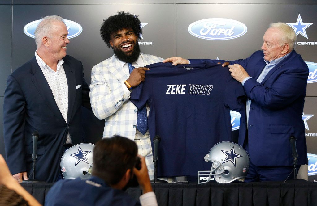 "Jerry Jones and Ezekiel Elliott (21) hold up a shirt saying ""Zeke who?"" as Stephen Jones laughs during a press conference about Elliott's contract extension at The Star in Frisco, Texas on Thursday, September 5, 2019. On the opposite side of the shirt it says ""That's who!"""
