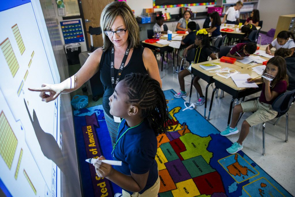 Third-grade teacher Bo Livingston helps Azariyah Shadd, 8, with a math problem on a projection board during class Wednesday at Donald T. Shields Elementary in Glenn Heights.