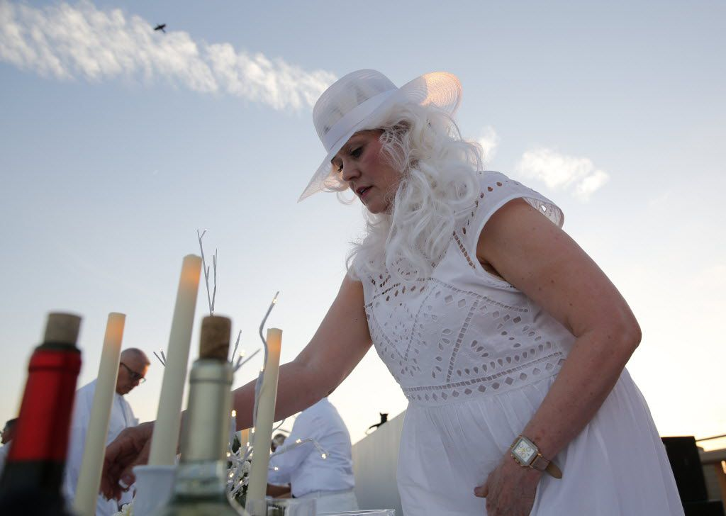 Penny Sanders sets the table during the inaugural Diner en Blanc Dallas on the Continental Avenue Bridge in Dallas on Sept. 17, 2015. Exactly 1,678 people attended the event, which requires dinner guests to dress all in white and bring their own tables, chairs and centerpieces. As per tradition, the location was kept private leading up to the event.