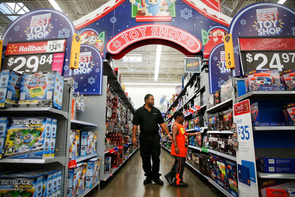 Joshua Williams, 8, walks with his dad Brian Williams down the toy aisle at Walmart in Dallas on Tuesday, Nov. 20, 2018. (Rose Baca/The Dallas Morning News)