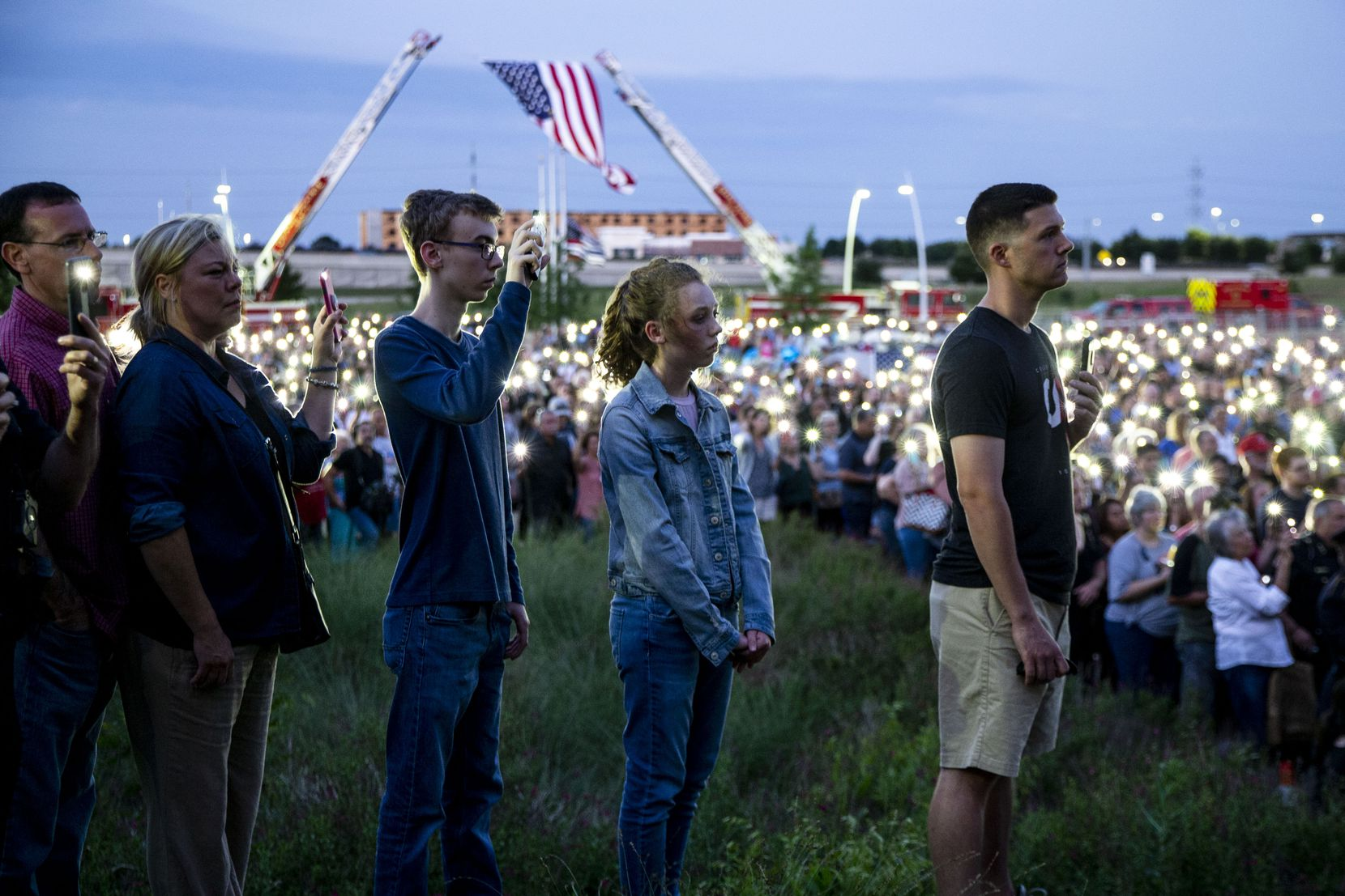 """Mourners hold aloft cellphone flashlights after high winds blew out candles during a vigil for Grand Prairie police Officer Albert """"A.J."""" Castaneda on Sunday at the Grand Prairie Public Safety Building."""