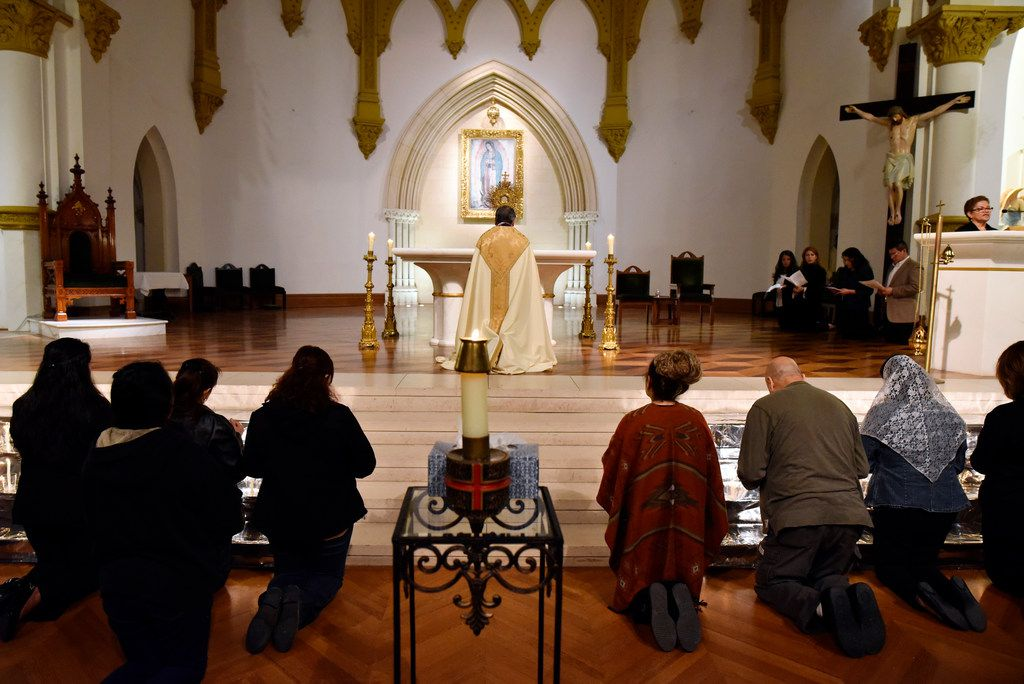 Priest Ruben Ortiz Montelongo, center, leads a prayer during a vigil for immigrants on Thursday, March 01, 2018 at the Cathedral Shrine of the Virgin of Guadalupe in Dallas.