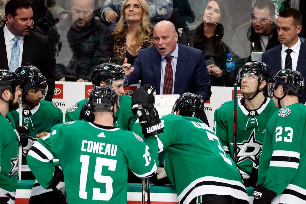 In this Jan. 30, 2019, photo, Dallas Stars head coach Jim Montgomery, center, instructs the team during a timeout of an NHL hockey game against the Buffalo Sabres in Dallas. Montgomery jumped right into the NHL from college coaching with the Stars, joining a team with immediate playoff expectations and finding himself in the middle of an unexpected drama after the surprising midseason rip job on star players Jamie Benn and Tyler Seguin by the CEO. The first-year coach had some strong words of his own along the way, and the Stars never lost their grip on a postseason spot after a decade of mostly missing out. (AP Photo/Tony Gutierrez)
