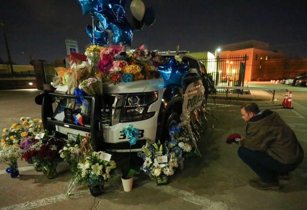 Flowers cover a police cruiser at the Richardson Police Station Thursday February 8, 2018. Officer David Sherrard was killed in the line of duty on February 7, 2018.
