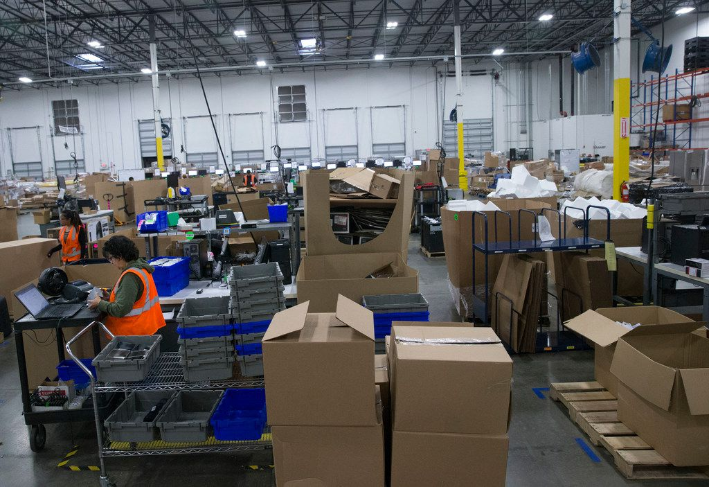 Warehouse specialist Carolina Merchant (bottom left) works at the Liquidity Services warehouse in Garland on Nov. 7, 2018. Warehouse general manager Scott Birlew (not pictured) said the warehouse receives items from food and automotive, to clothing and electronics.