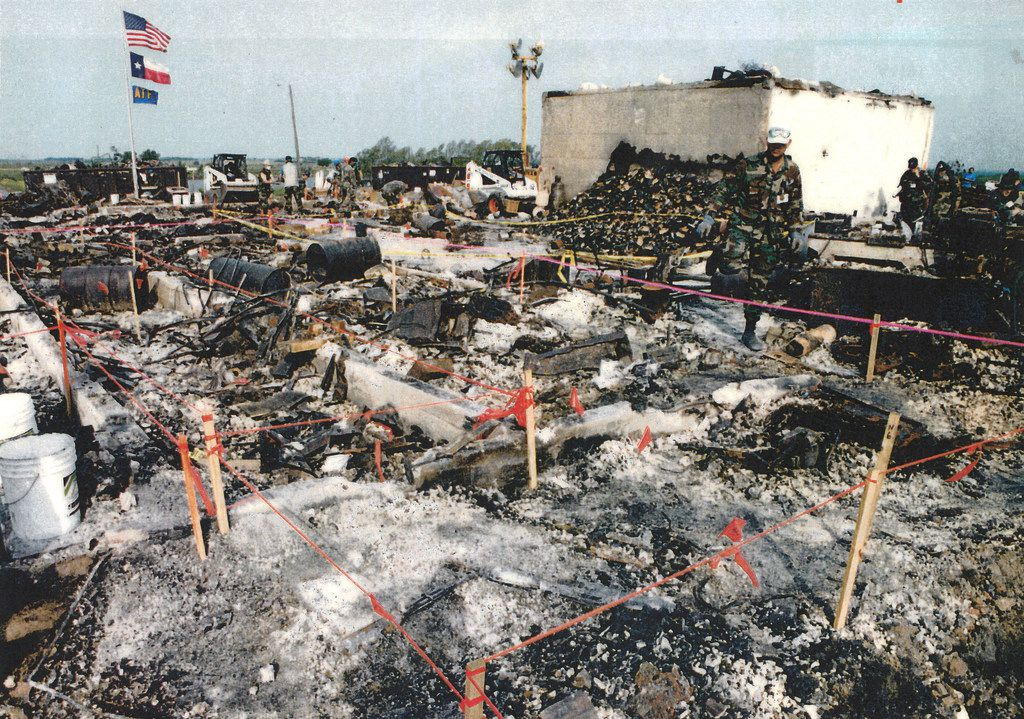A government photo of U.S., Texas, and AFT flags which law enforcement raised over the charred rubble of the Branch Davidian compound after the standoff and siege resulted in the fire that killed more than 70 people.