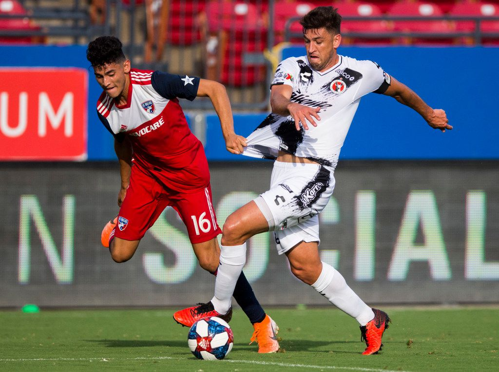 FC Dallas forward Ricardo Pepi (16) gets ahold of the jersey of Club Tijuana defender Diego Braghieri (6) during the first half of a friendly MLS game between FC Dallas and Club Tijuana on Sunday, July 7, 2019 at Toyota Stadium in Friso. (Ashley Landis/The Dallas Morning News)