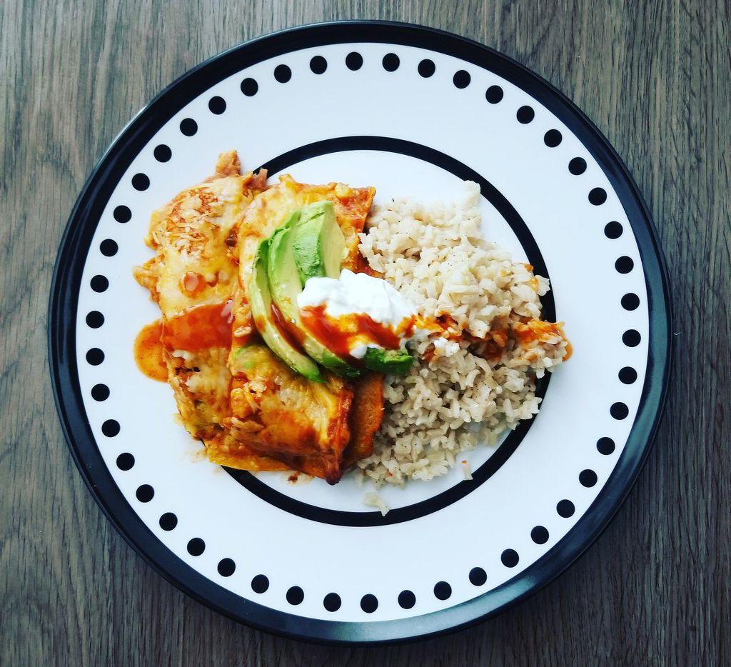 Veggie enchiladas served with rice and avocado.
