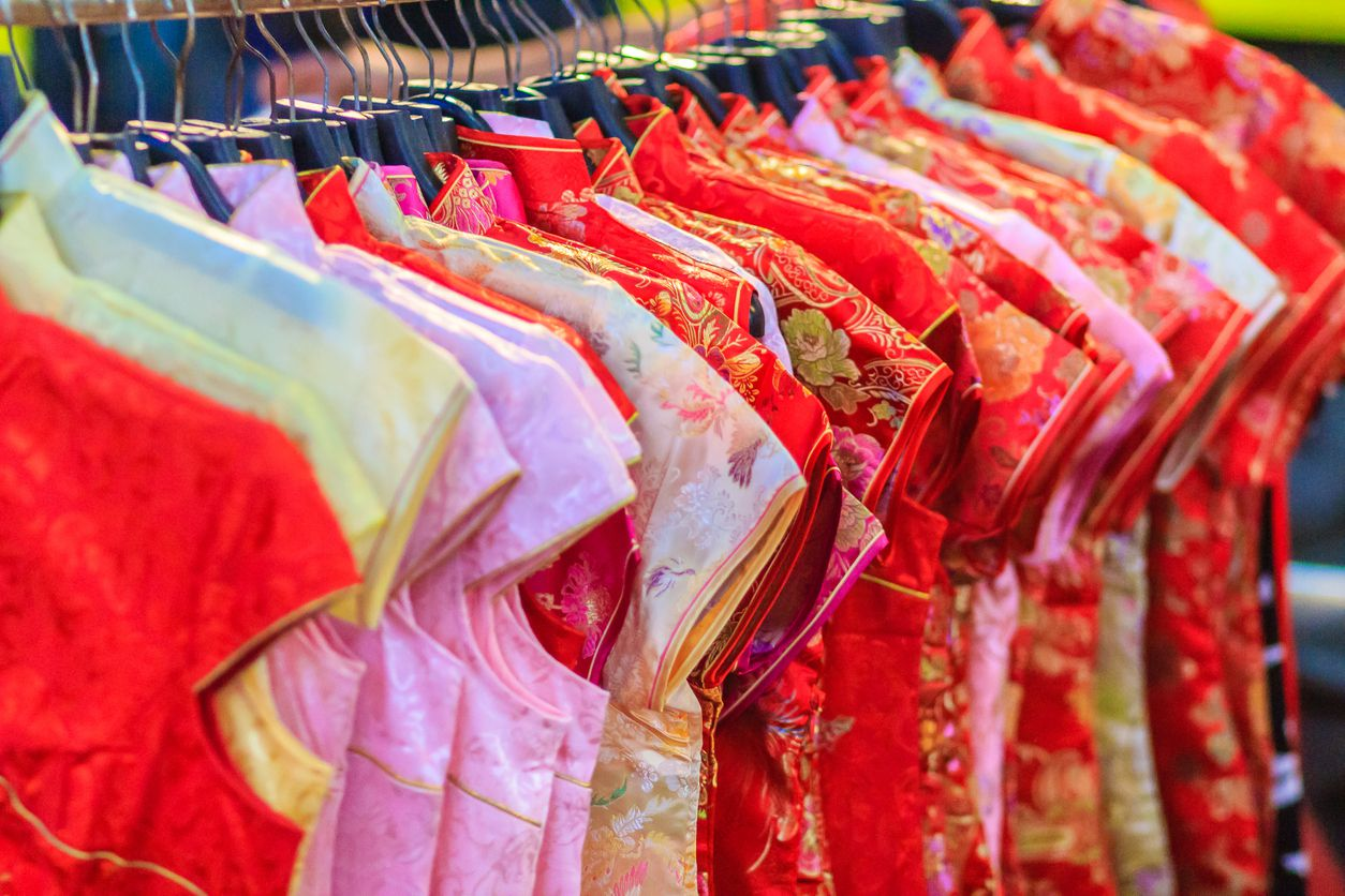 Beautiful Qipao (cheongsam dress or Chinese dress) for women hanging on a clothes line in night market for sale to customers during the festival is Chinese New Year at Bangkok, Thailand.