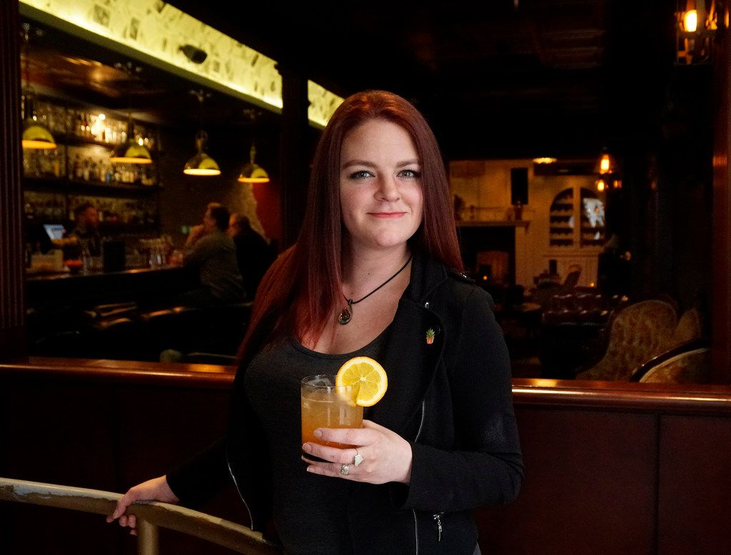 Thompson's Bookstore beverage director Brittany Day holds a mocktail at the bar in Fort Worth. The non-alcoholic drink is made with orange juice, pureed strawberries, cinnamon syrup and ginger ale with ice and an orange slice.