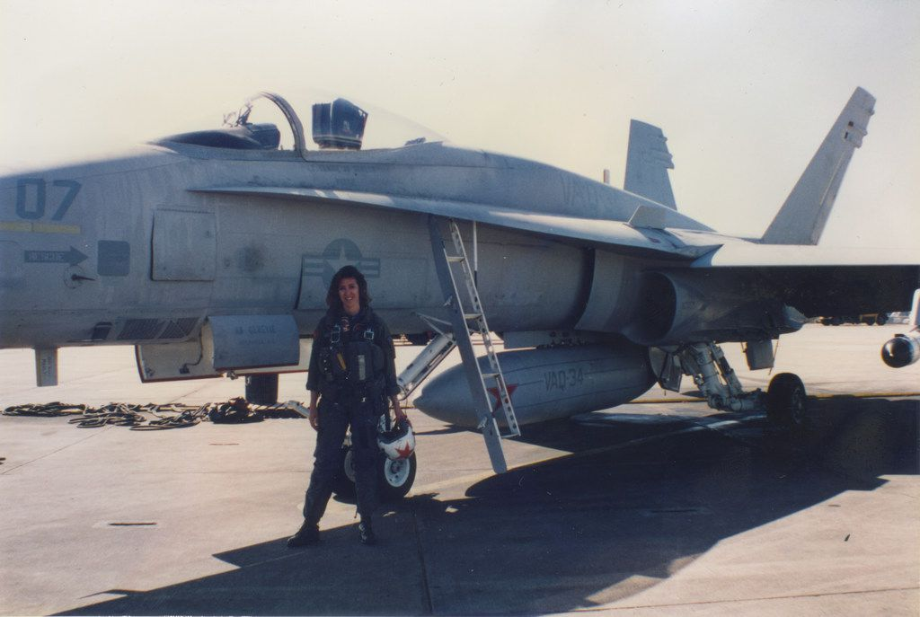 Pilot Tammie Jo Shults in front of a Navy jet.