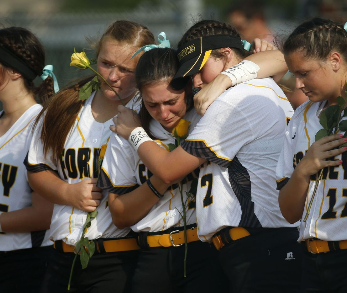 Forney softball players Sam Coker (left) and Savannah DesRochers (2, right) embrace Caroline Tedder (30, middle) during a moment of silence for their teammate Emily Galiano before the regional semifinal game against Mansfield Lake Ridge at Kennedale High School in Kennedale on May 18. The game was played just two days after Emily was struck and killed by a vehicle after leaving a team dinner party.