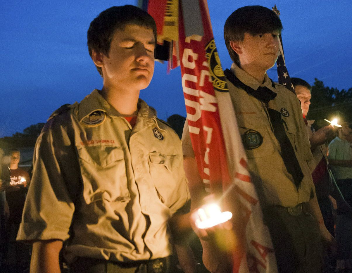Ian Sullens, of Troop 621, left, and Samuel Powers of Troop 201 participate in a candlelight vigil Sunday, Aug. 6, 2017, in Hallsville, Texas, for two fellow scouts who were killed killed and another severely injured in a Saturday boating accident.