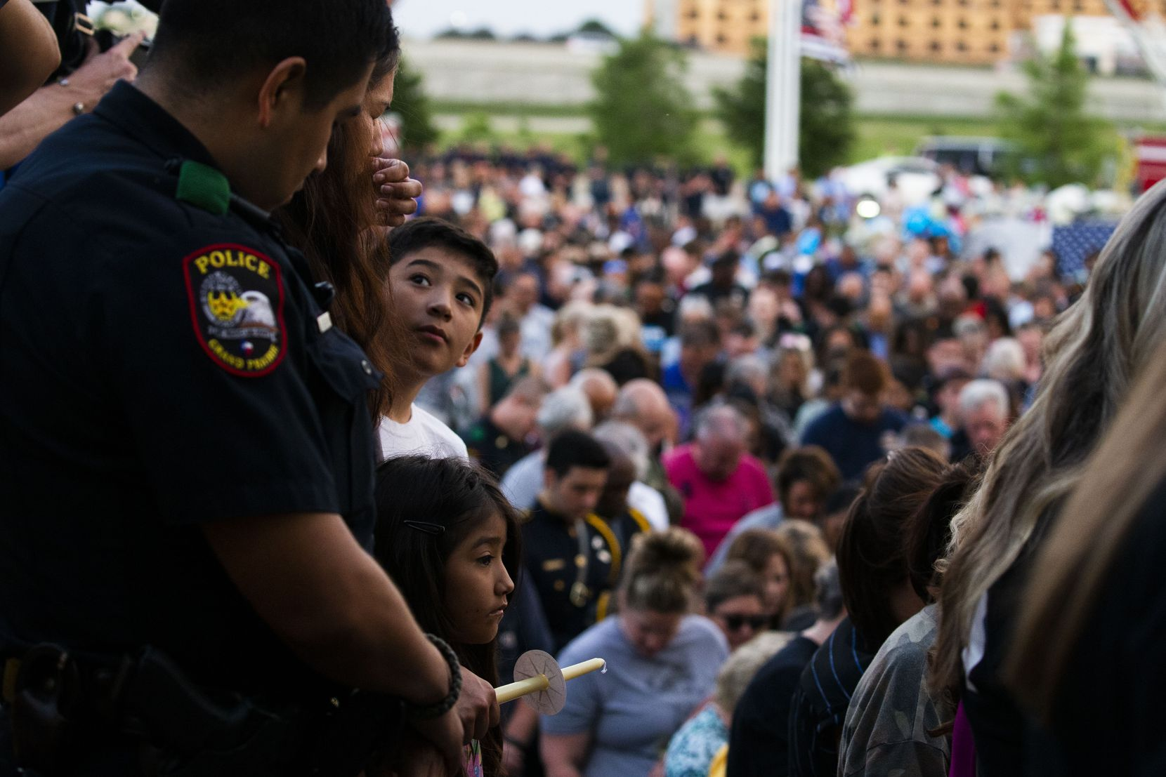 """Eric Molina looks up at his father, Grand Prairie police Officer Edgar Molina, as his sister, Rebecca Molina, 6, looks on during Sunday's vigil for Officer Albert """"A.J."""" Castaneda at the Grand Prairie Public Safety Building."""
