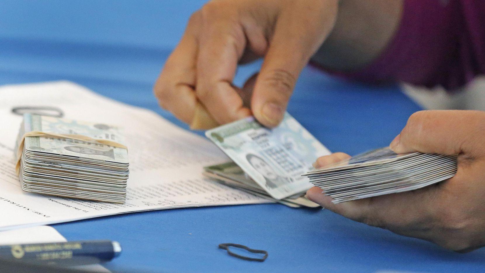 Una funcionario de inmigración pone en orden tarjetas de residencia permanente. (DMN/Louis DeLuca)