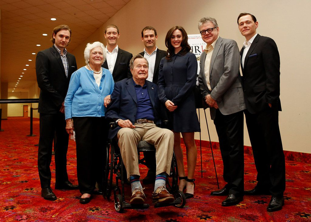 Former President George H.W. Bush, former first lady Barbara Bush, and the cast of the AMC series TURN attended a private screening on March, 29, 2014, in Houston. Heather Lind stands next to Bush.