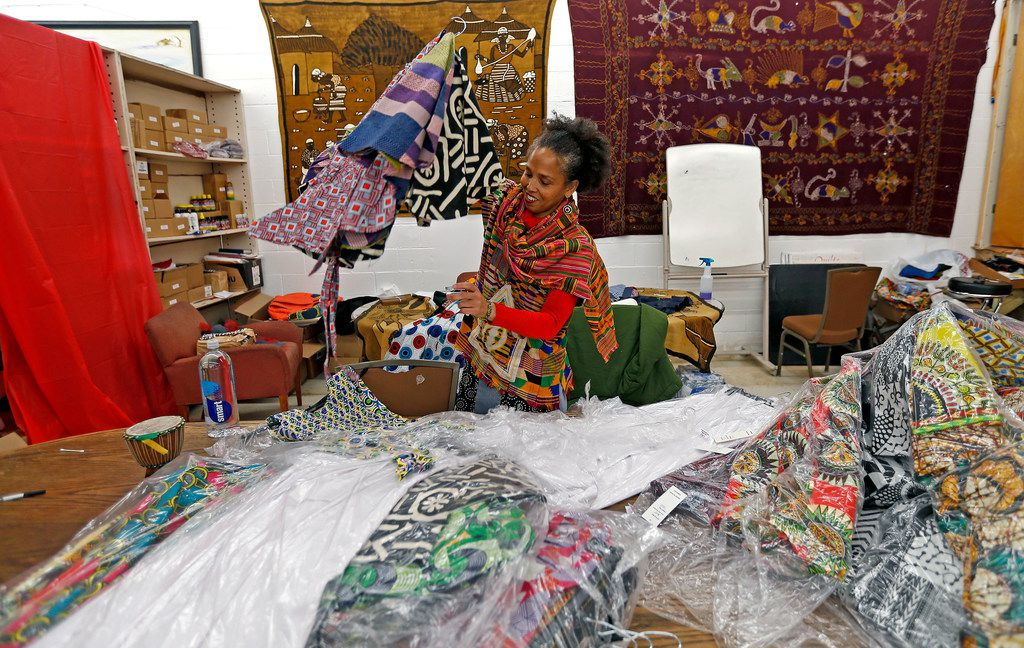 Owner Akwete Tyehimba sorts out dresses in February at Pan-African Connection in Dallas.