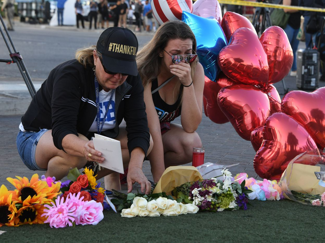 Destiny Alvers (R) who attended the Route 91 country music festival and helped rescue her friend who was shot, reacts at a makeshift memorial on the Las Vegas Strip in Las Vegas, Nevada on October 3, 2017, after a gunman killed 59 people and wounded more than 500 others when he opened fire from a hotel window on a country music festival. Police said the gunman, a 64-year-old local resident named as Stephen Paddock, had been killed after a SWAT team responded to reports of multiple gunfire from the 32nd floor of the Mandalay Bay, a hotel-casino next to the concert venue. / AFP PHOTO / Mark RALSTONMARK RALSTON/AFP/Getty Images