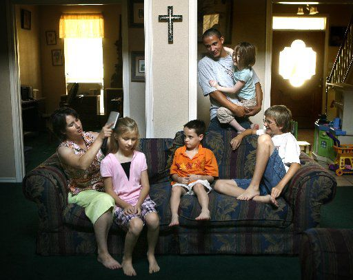 Former foster parent Shannon Waters (left) and her biological children Sam Waters, 10, (in pink, in her lap); Alex Waters, 12, (in longhorns shirt, right), and her adopted kids, Chris Waters, 17, holding Daxie Waters, 6, and Dillon Waters, 7, (orange shirt,center),. Shannon and her husband Bill of Granbury just quit foster parenting because of frustrations over state rules and incorrect information from CPS caseworkers about the severity of the youngsters behavioral disorders. They had taken care of more than 70 foster children in seven years in their five bedroom house. Dillon was their first foster child. (2007 staff file photo/Tom Fox)