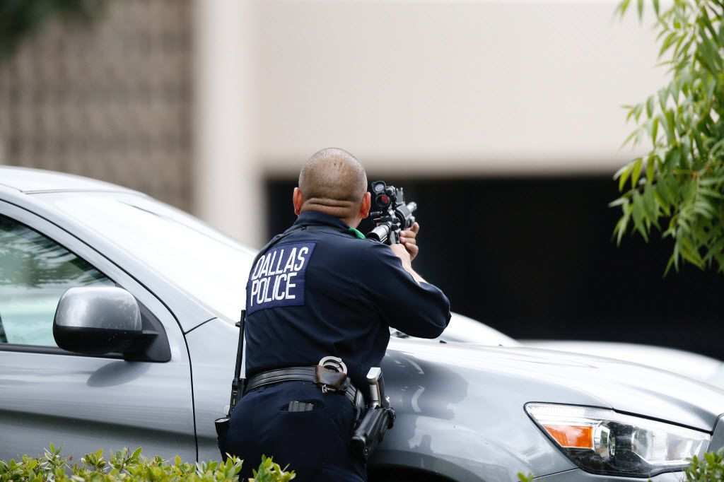 A Dallas police officer on alert at Dallas Police Headquarters where a credible threat was recieved on Saturday, July 9, 2016.