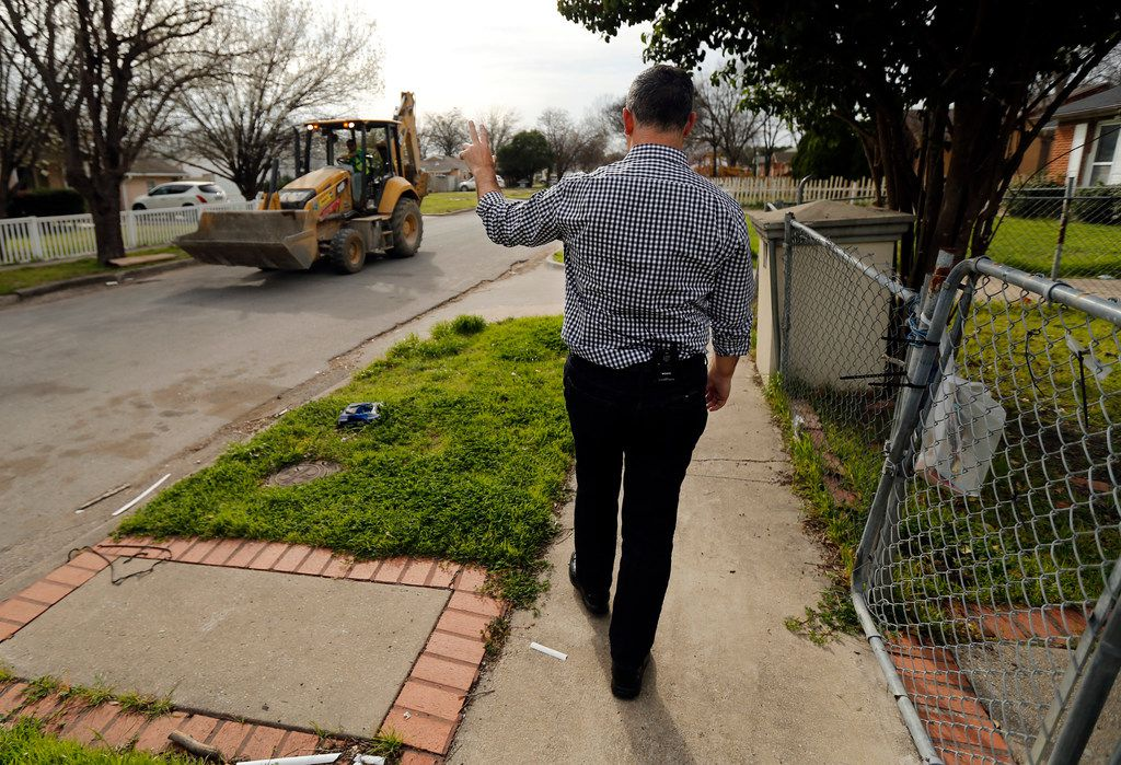 """Rep. Rafael Anchia waves to a backhoe operator as he walks the Northwest Dallas neighborhood plagued by natural gas leaks where Linda """"Michellita"""" Rogers' died last year in a natural gas explosion in her home."""