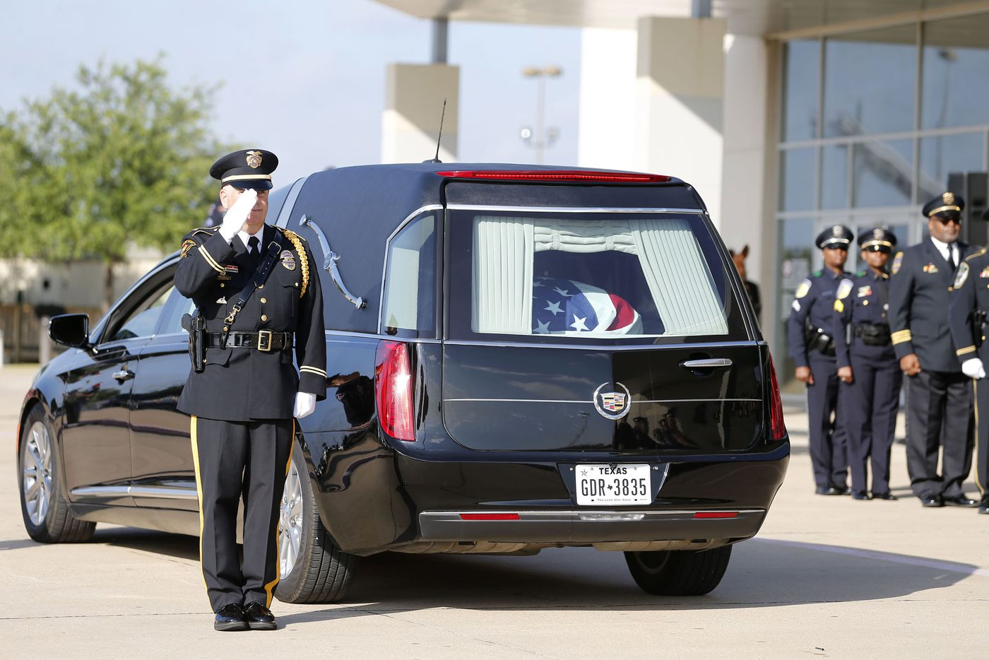 An officer salutes as a hearse arrives carrying DART Officer Brent Thompson in preparation for a memorial service at The Potter's House in Dallas on Wednesday, July 13, 2016. Thompson was one of five officers killed last week when a gunman opened fire during a Black Lives Matter rally in downtown Dallas.