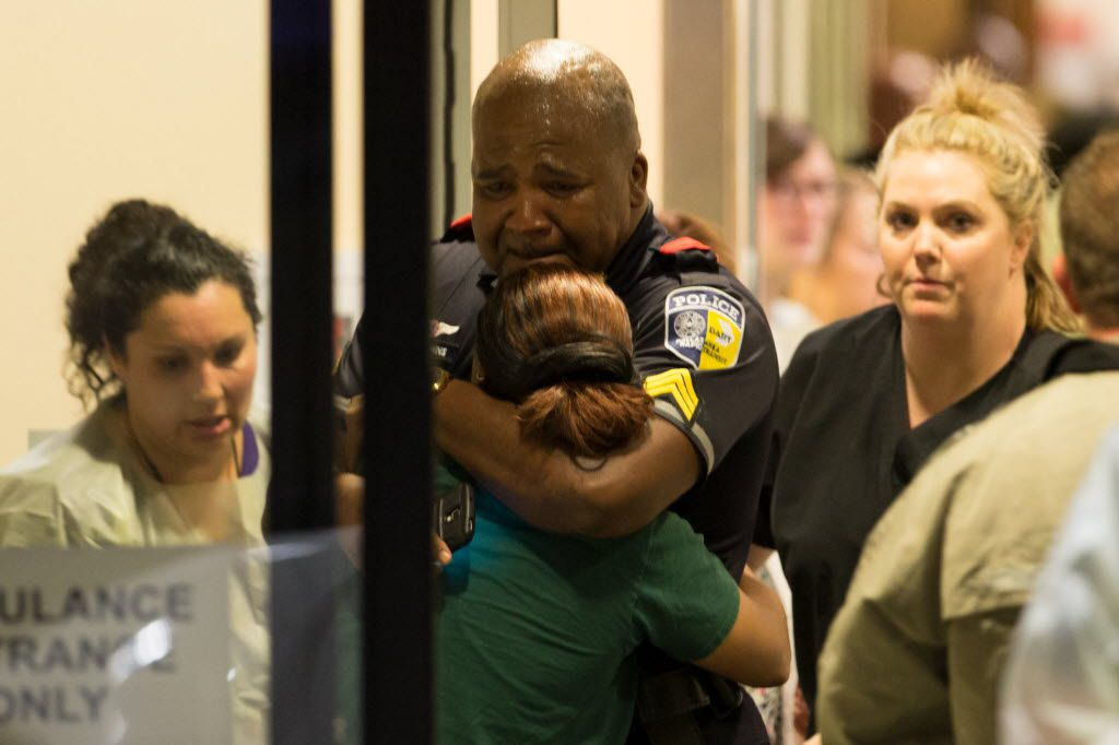 A DART police officer hugs another officer at Baylor University Hospital's emergency room entrance on July 7 in Dallas after five police officers were killed by an enraged gunman in downtown Dallas at the end of a march protesting police shootings of black men around the country.