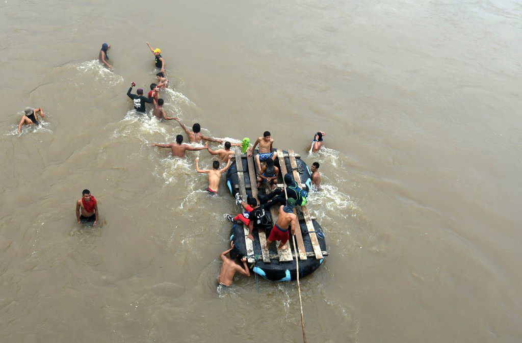 Honduran migrants heading in a caravan to the US, try to reach Mexico through the Suchiate River, in the border city of Tecun Uman on October 19, 2018.
