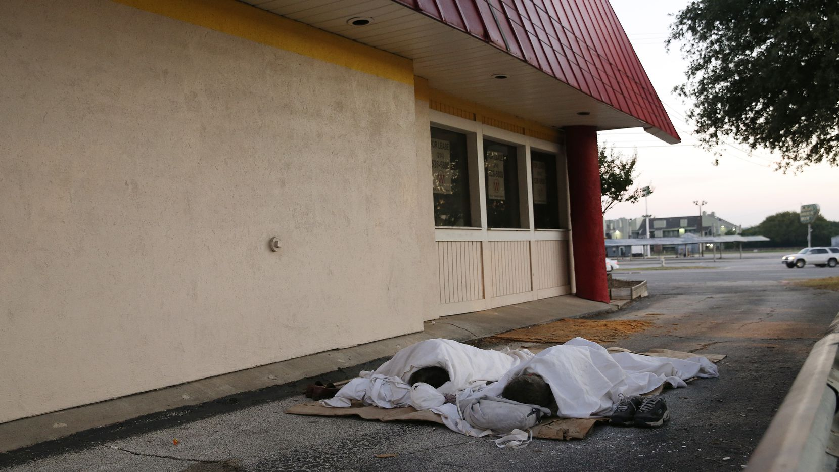 Two homeless men sleep in the driveway of a closed payday loan store located at 6534 East Northwest Highway in Dallas, Texas on Thursday September 25, 2014. Dozens of payday loan stores in Dallas have closed since the city passed a landmark ordinance regulating the lenders three years ago. It's just one way, city officials and consumer advocates said, that the ordinance has had an impact on an industry that they say preys on low-income residents and traps them in a cycle of debt. (David Woo/The Dallas Morning News) 09282014xNEWS